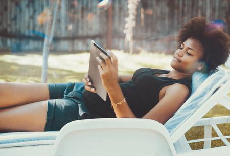 Feminino adolescente negro pensativo no sofá-cama no parque público é navegar na net com teclado digital; jovem bela e afro-americana é relaxante na cadeira de tábua com tablet pc no jardim de verão
