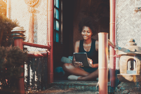 Charming smiling afro teenage female is sitting on the porch of summer house with tablet pc; young cheerful Brazilian woman with curly hair working with digital pad while sitting on veranda of pagoda