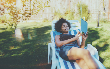 Beautiful young black female with curly African hair is laying on the striped daybed in the city park and browsing net using digital tablet with copy space place for advertising, your logo or text