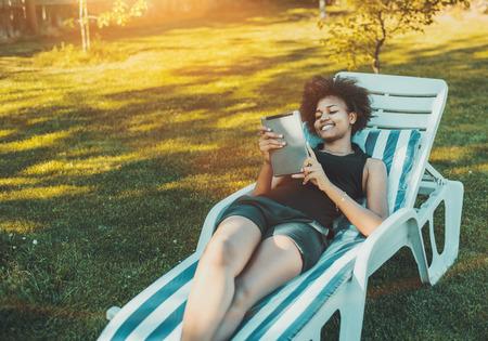 A jovem brasileira alegre está deitado na poltrona reclinável e ligando o vídeo com a família através do tablet pc em um dia ensolarado no parque com espaço para cópia do anúncio, seu logotipo ou uma mensagem de texto