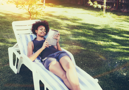 Young black teenage lady is laying on a wooden recliner on the glade of garden and messaging via tablet pc; cute curly afro female student reading her homework articles via digital pad in the park Stock Photo