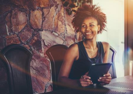 Jovem estudante brasileira alegre com cabelos encaracolados e africanos est Banco de Imagens