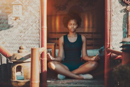 Jovem encantadora mulher afro-americana com cabelos encaracolados sentada dentro do pagode oriental em um tapete e meditando, halo apareceu ao redor de sua cabeça, ela está sentindo calma e calma, alcançou o nirvana