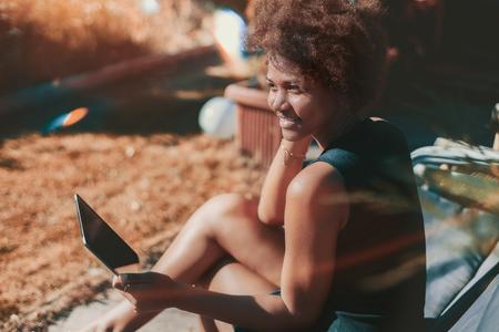 Adolescente preta alegre e alegre, sentada ao ar livre na poltrona e olhando para o lado enquanto segurava uma almofada digital; jovem brasileira encantadora está sorrindo enquanto está sentado no parque de outono com tablet pc