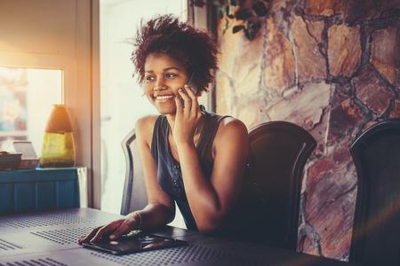 Sorrindo atraente jovem afro-americana com cabelos encaracolados está sentada no quarto escuro do terraço e conversa por telefone com sua amiga; Tablet PC na mesa, janela com flare em segundo plano