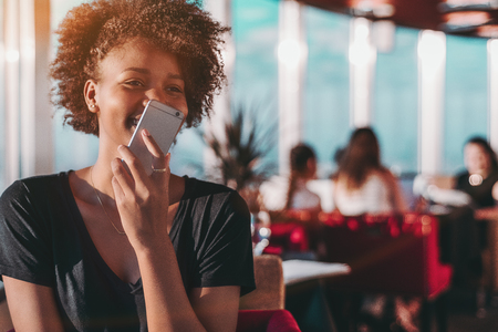 Appealing young Brazilian female is sitting in restaurant and laughing while dictating audio message on her smartphone with people in blurred background and copy space place for your advertising
