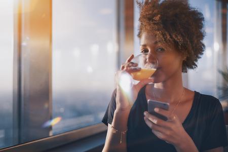 Dainty jovem afro-americana curly feminino sentada sozinha no restaurante ao lado da janela e beber suco de laranja do copo em pausas entre seu bate-papo on-line que ela faz usando seu smartphone Banco de Imagens