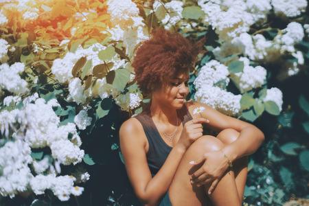 Glamorous jovem estudante de cachorros pretos e curly está sentada durante o intervalo na frente de belas flores brancas que estão florescendo em um jardim de seu campus universitário e segurando camomila