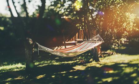 Verdadeira visão de mudança de inclinação da rede de lixo vazio esticada entre duas macieiras no jardim em um dia ensolarado com uma cerca em segundo plano e prado com brilhos de sol em primeiro plano defocused