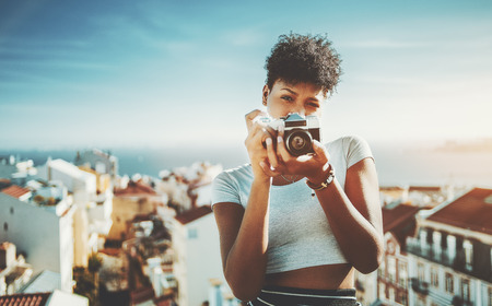 Portrait of curly biracial lady with retro photo camera and city with sea in blurred background; young black female with vintage camera and copy space for logo, text or your advertising; Lisbon city Foto de archivo