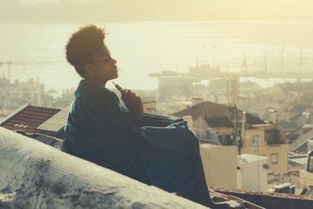 Adorável garota encaracolada está sentada no telhado da cidade costeira enrolada em um tapete em um dia ensolarado e gosta de fumar cigarro eletrônico; paisagem urbana desbotada com rio, porto e casas em segundo plano