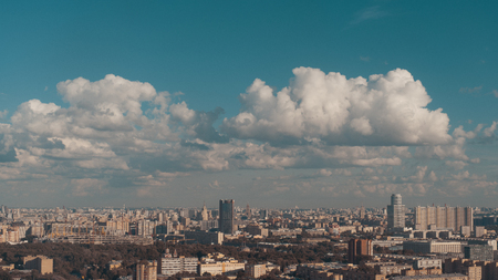 View from high elevation of metropolis summer cityscape with multiple residential and office buildings, high-rises, public parks and stadium under construction; beautiful cloudscape; Moscow, Russia
