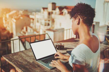 Vista por trás da senhora curvatura biracial na varanda usando seu laptop com modelo de tela em branco; Vista traseira da jovem fêmea afro-americana trabalhando com seu netbook com maquiagem de tela branca vazia
