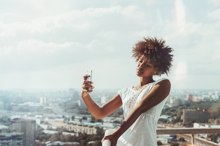 Exquisite young African American lady with curly hair is taking selfie using camera of smartphone while standing on the balcony of high skyscraper with summer cityscape in defocused background Foto de archivo