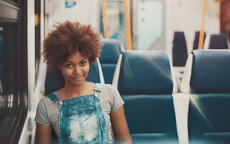 Smiling good-looking young black curly female in denim overalls is sitting near window inside of evening suburban train with empty seats behind and copy space place for advertising or text message