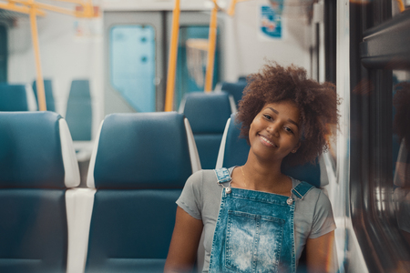 Young appealing cheerful African American female with curly hair in denim overalls is sitting alone in suburban train carriage next to window with copy space place for text or advertising message