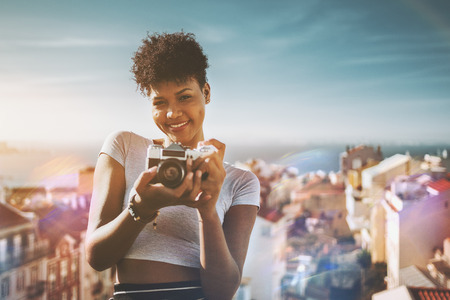 Portrait of young smiling glamorous African American female holding retro film camera with colorful cityscape behind; cheerful Brazilian girl with vintage photo camera and city with sea behind her Foto de archivo