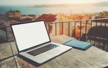Laptop moderno com mockup de tela em branco e trackpad enorme na mesa de madeira ao lado do tablet pc; netbook com modelo de tela branca vazia perto de tablet digital em espaço de trabalho de varanda com paisagem urbana borrada