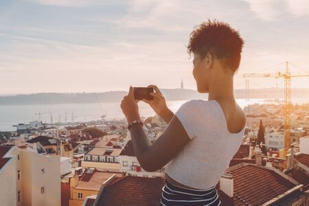 Side view of curly African American female standing on the roof of house and taking panoramic shoot on her smartphone; sunny day, Lisbon city with Tagus river and residential area in background