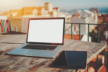 Espaço de trabalho aconchegante na varanda da casa com vista da paisagem urbana européia em fundo defocused; laptop moderno na mesa de madeira com modelo de tela em branco branco e tablet digital perto dele, dia ensolarado