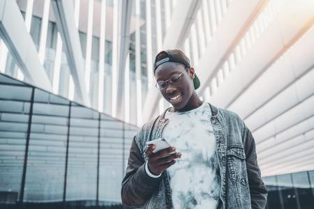 Estudante sorridente afro-americano em gafas, bon Banco de Imagens