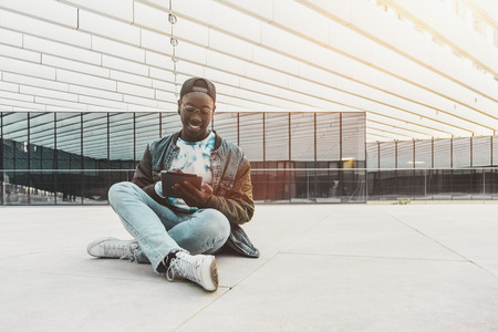 Cheerful young black student is sitting on the stony floor outdoors in modern university campus and having online chat with his friends via tablet pc with copy space place for advertising or your logo
