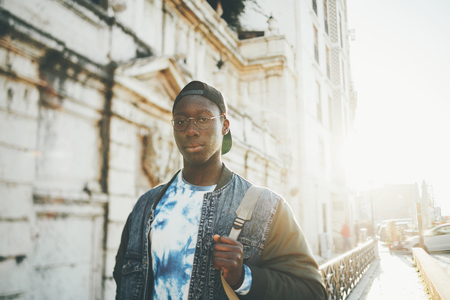 Handsome tall young black student guy with backpack on street of Lisbon near old house; African undergraduate male nerd in round glasses and denim jacket is going to university on pavement street
