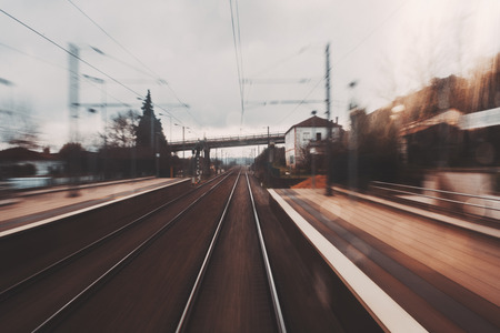 View from the last carriage of fast train of: station platform, bridge in a distance, railway tracks stretching into the distance, houses, poles with wires and evening moody sky; strong motion blur Standard-Bild