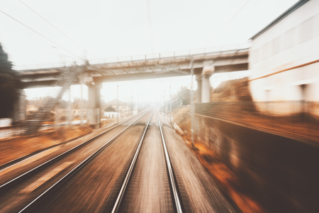 View from cabin of high-speed suburban train on autumn evening: railway tracks going to vanishing point, autumn grass, bridge, pillars with wires, station and buildings; strong motion blur