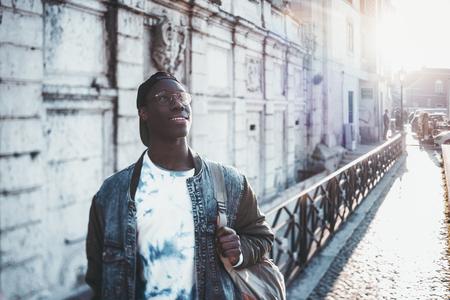 O estudante de estudante africano bonito em uma jaqueta de jean e  Banco de Imagens