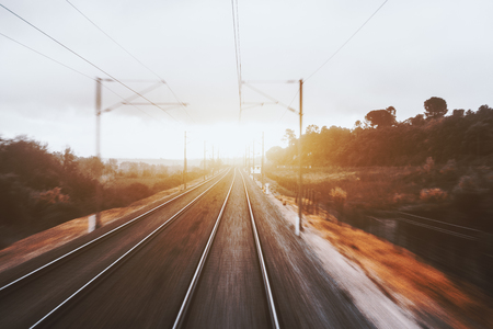 View from cabin of high-speed suburban train on sunset: railway tracks going to vanishing point, autumn grasslands, trees, pillars, wires, sun flare and trees; strong motion blur