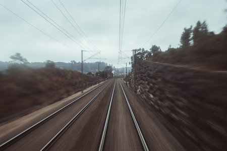 Photo shooting from the last coach of a high-speed train: dry autumn landscape with dull sky, two railway tracks stretching into distance, stone wall, plants and trees, poles and wires Banco de Imagens