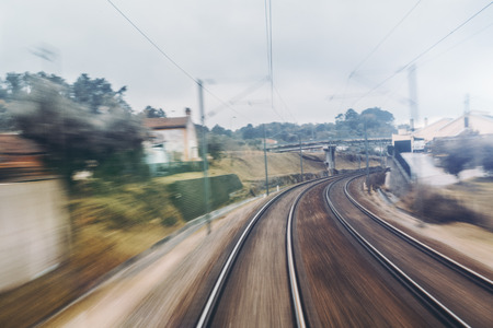Long exposure shooting with strong motion blur from cabin of high-speed suburban train: turn right under the bridge, two railway tracks, buildings, poles with wires, summer morning Banco de Imagens