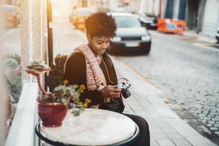 Exquisite young Brazilian tourist girl in coat and muffler is sitting at the marble table of street cafe next to sett paving and looking through photos on screen of her retro looking film camera