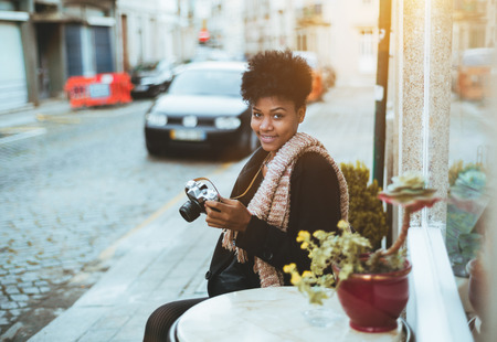 Happy young African American woman is sitting alone at street bar of Europian city, looking at camera and holding old vintage photo camera; smiling Brazilian girl with retro film camera in street bar