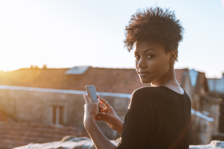 Young serious exquisite black female is photo shooting sunset while standing on the roof and looking at camera; portrait of Brazilian girl using smartphone while standing on the balcony of house