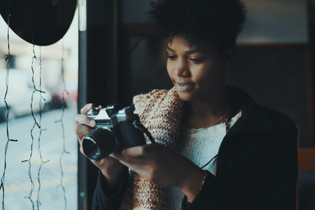Beautiful curly black girl with vintage photo camera indoors; Brazilian cheerful brunette female photographer in dark cafe near window with retro film camera looking through captured footage