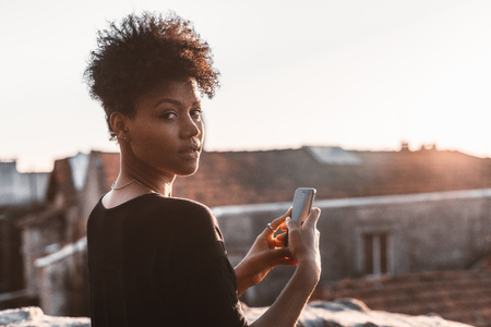 Portrait of young appealing Brazilian female standing on the roof and taking pictures using her smartphone; lovable black girl standing on a balcony in half a turn to camera and using her cellphone