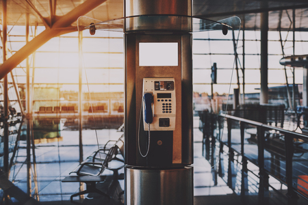 Close-up view of push-button payphone in opened transparent phone booth located in modern airport terminal or contemporary shopping mall interior, or railway depot station with waiting hall behind