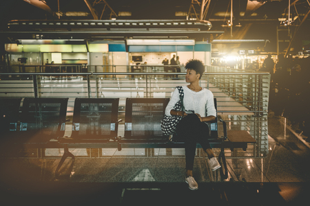 Beautiful young Black female tourist is sitting inside of modern airport terminal and waiting for her flight; cute Brazilian girl with curly Afro hair is sitting in waiting hall of railway station