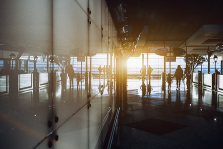 Silhouettes of several moving off people inside of interior of modern airport terminal or railroad depot station, or shopping mall; with white reflective glass wall, cafe fencing and windows behind Foto de archivo