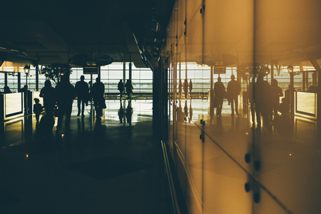 Silhouettes of going people inside of dark interior of contemporary airport terminal or railroad depot station, or shopping mall; with white reflective glass wall, cafe fencing and windows behind