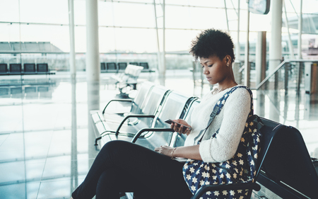 Portrait of young sweet Brazilian tourist girl in white pullover, with backpack sitting in waiting room of airport terminal or railway station depot, or shopping mall and messaging using smartphone