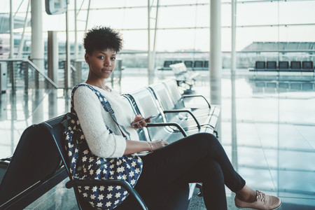 Portrait of young lovable Brazilian girl with curly Afro hair sitting on armchair in airport terminal waiting hall or in modern railway depot station interior, looking at camera while using smartphone