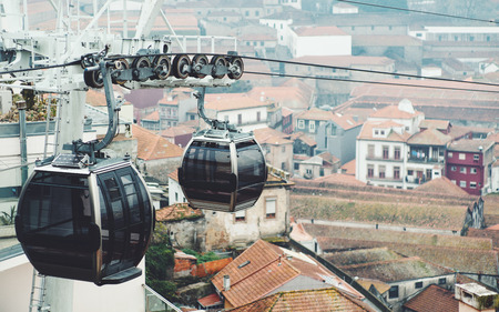 Two empty modern cable cars made of black glass and chrome with solar batteries on top are passing ropeway section with gears and wheels; facades and tile roofs of old historical houses in background Foto de archivo
