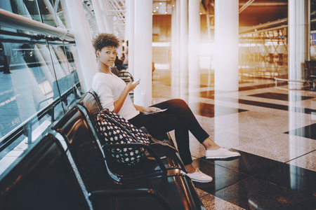 Dazzling young Brazilian traveler girl is sitting in armchair seat in waiting hall of modern airport terminal or railway station depot, holding tickets and using smartphone to check departure details