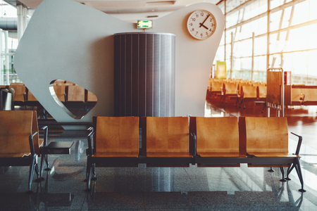 Modern waiting hall in departure area of airport with rows of empty seats; railway station depot waiting room with wooden seats and figured wall behind with clock and glass facade in background