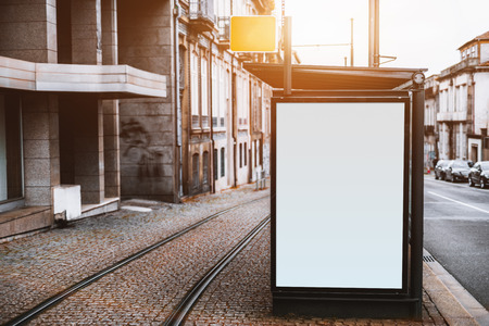 Close-up view of empty white informational banner mockup in urban settings between road and tramway; blank billboard placeholder template outdoors on city tram stop, pavement stone, sunny day Foto de archivo