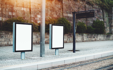 Template of two empty city billboards on train station outdoors or metro station; mock-up of blank informational banners in urban settings near tram stop with electronic indicator panel behind Foto de archivo