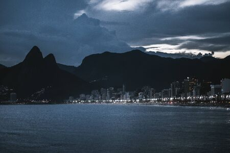 Night view of Ipanema and Leblon beaches of Rio de Janeiro shore with city and Two Brothers mountains in the background: night lights of hotels, swimming people, dark sky, ocean in foreground, Brazil
